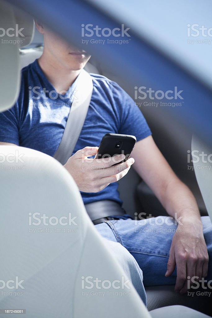 Passenger in car using smart phone stock photo