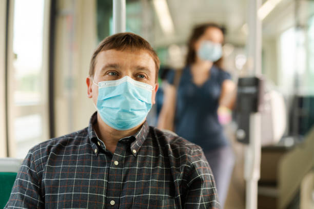 Passenger in disposable mask in city streetcar stock photo