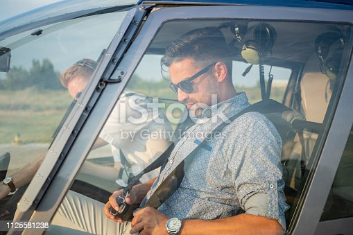 Passenger sitting with pilot in helicopter cockpit and fastening his seat belt