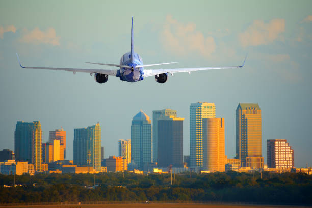 Passenger jet airliner plane arriving or departing Tampa International Airport in Florida at sunset or sunrise stock photo