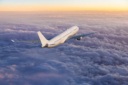 Passenger jet airplane flying above clouds at sunset