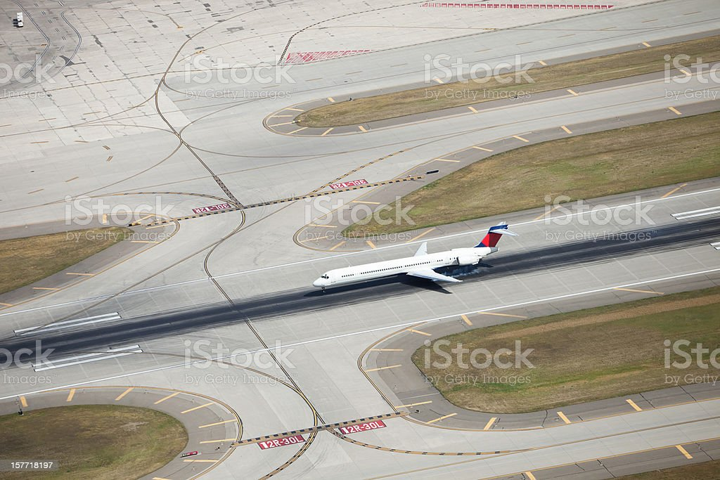 Passenger Jet Landing on Runway, with Smoking Tires, from Above stock photo
