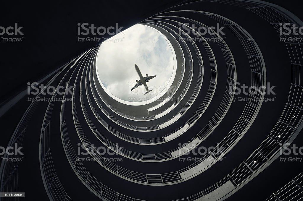 Passenger jet seen through top of multi level car park stock photo