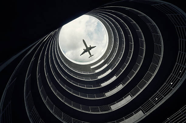 Passenger jet seen through top of multi level car park stock photo