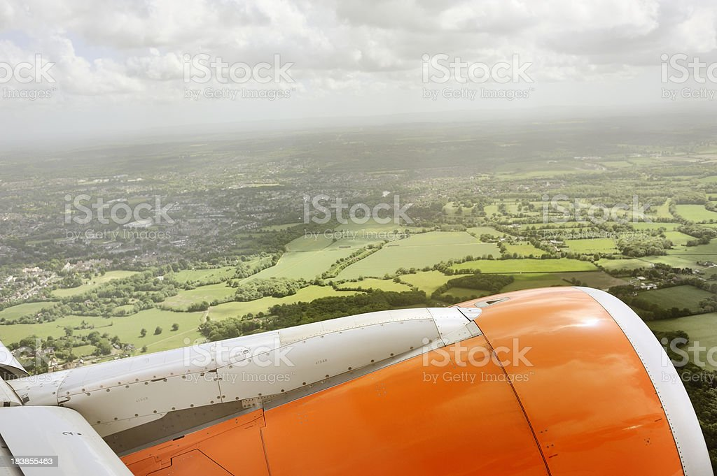 Passenger Jet Takes-off Over Green Fields stock photo