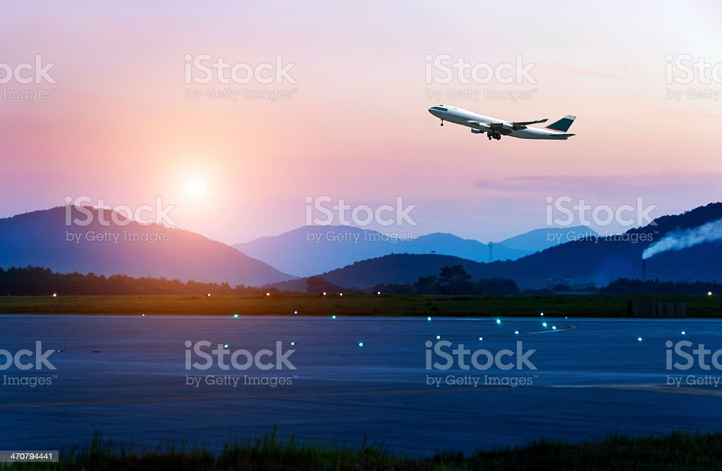 Passenger jet taking off from a runway beside mountiains stock photo