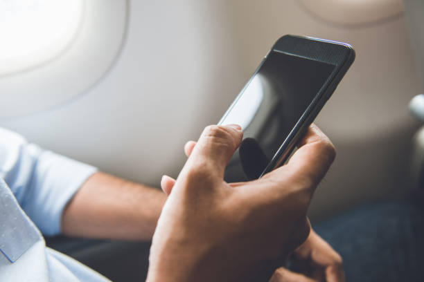 Passenger just turned off mobile phone on the airplane while traveling for safe flight stock photo