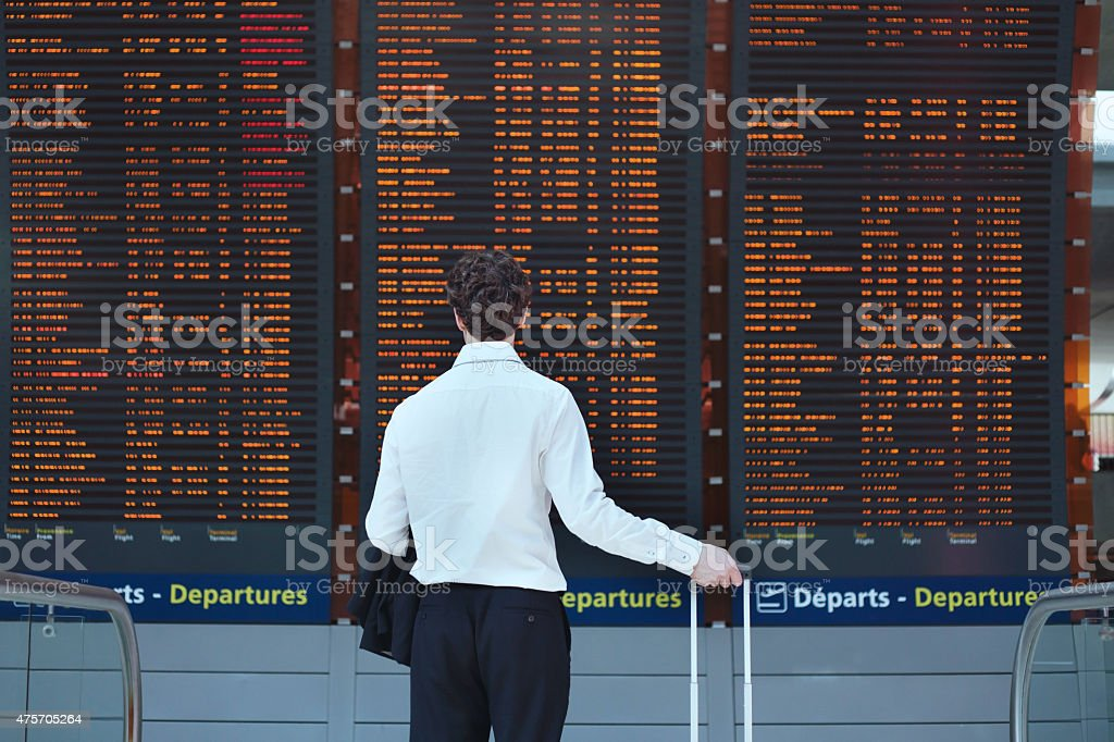 passenger looking at timetable board stock photo