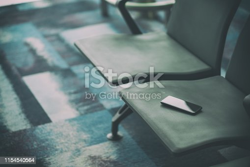 istock Passenger lost mobile phone on the airport chair 1154540564