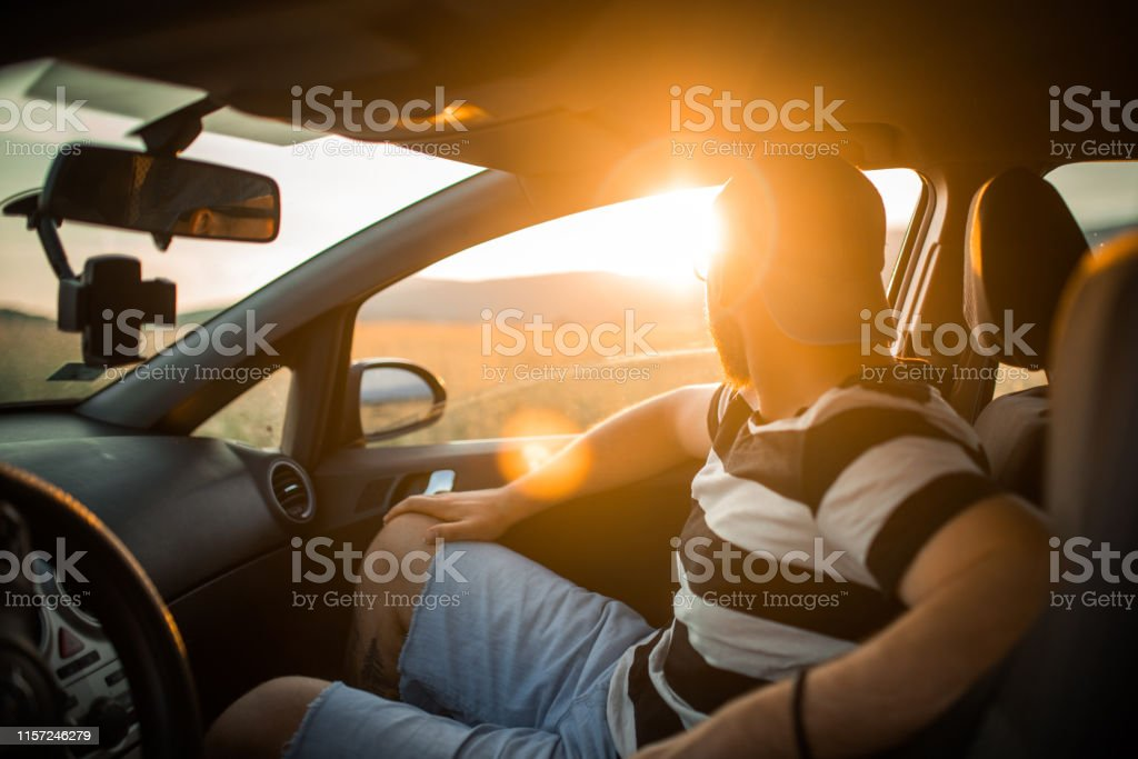 Young man with sunglasses and cap in car on a road trip on country...