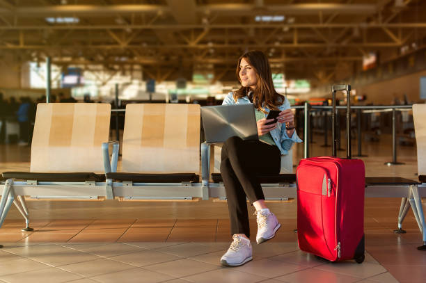 Passenger on smart phone and laptop sitting in airport terminal hall stock photo