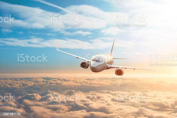 Photo of Passenger plane, business trip, travel concept. Flying evening sunset.