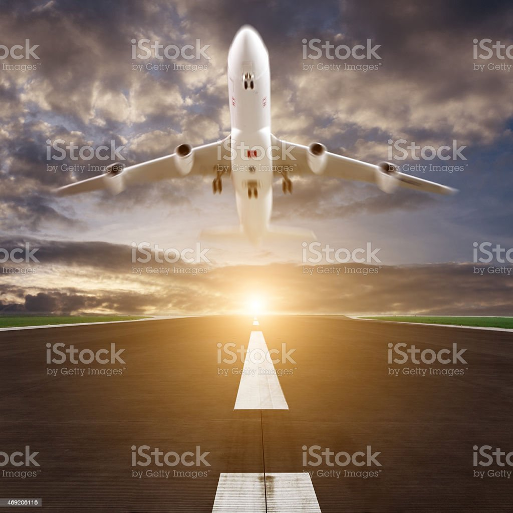 passenger plane fly up over runway from airport at sunset stock photo