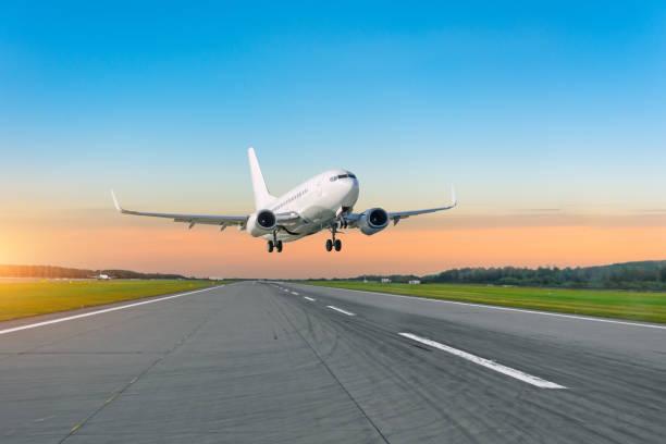 passenger plane fly up over take off runway from airport at sunset. - lądować zdjęcia i obrazy z banku zdjęć