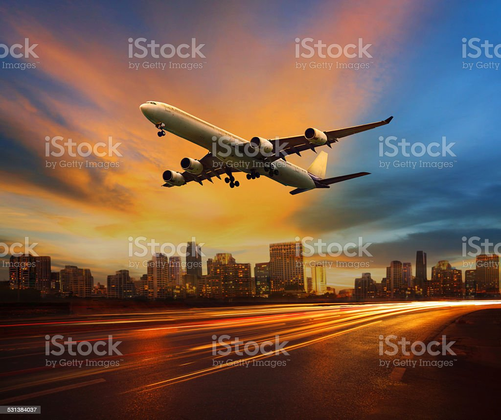 passenger plane flying above lighting of urban scene stock photo