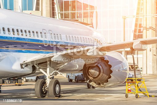186763256istockphoto Passenger plane is parked in front of the terminal for preflight maintenance and fueling 1133863119