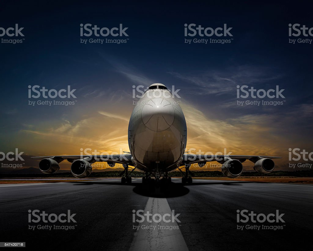 Passenger plane on runway at sunset stock photo