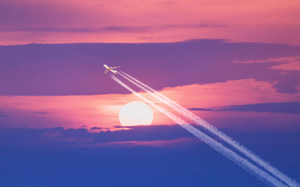 Passenger plane passes near the sun stock photo