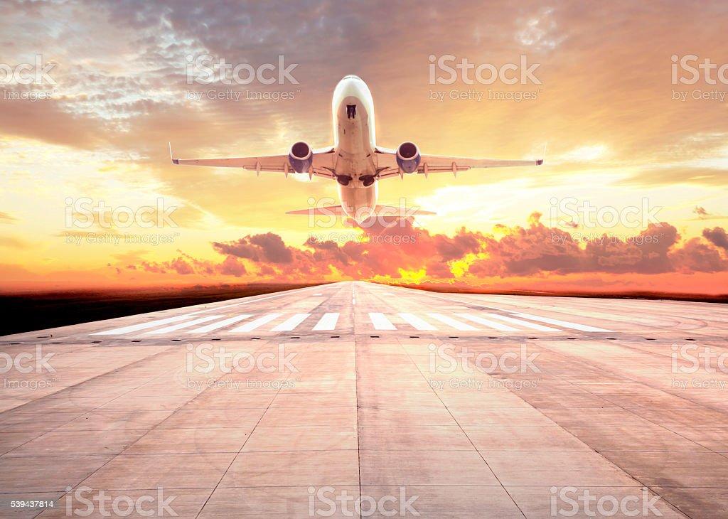 Passenger plane take off on sunset stock photo