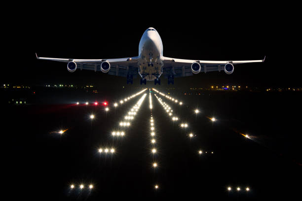 A passenger plane takes off from the night airport runway A passenger plane takes off from the night airport runway. Airplane front view. airfield stock pictures, royalty-free photos & images