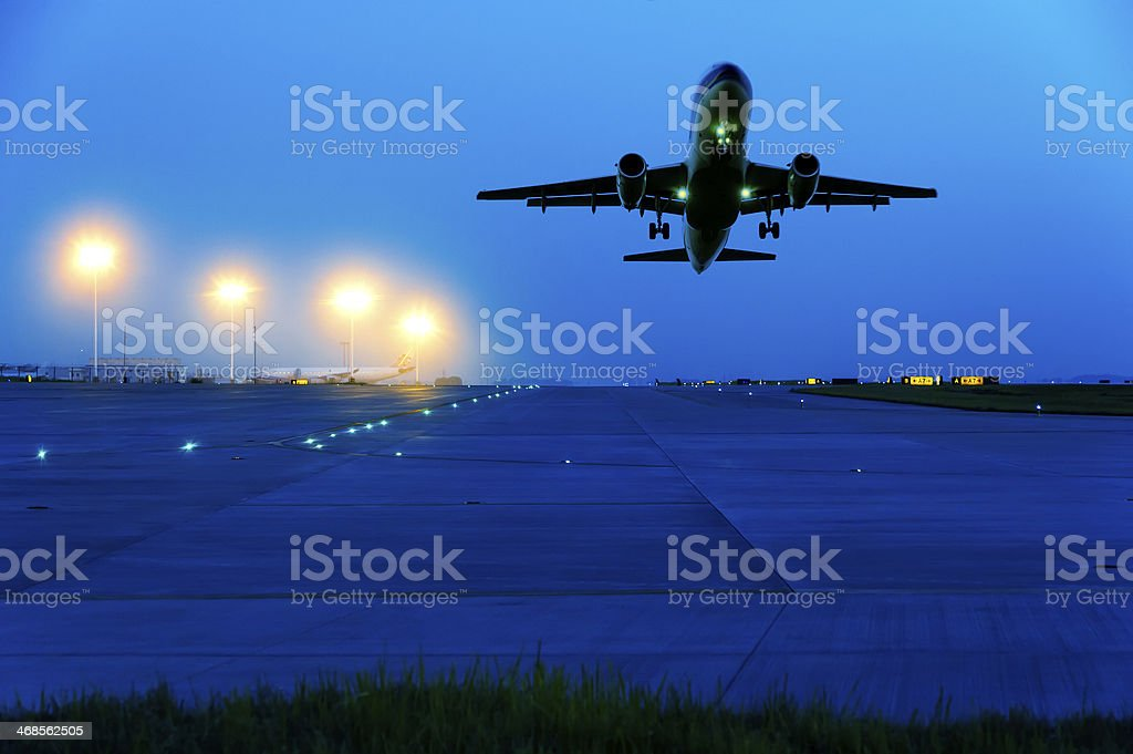 Passenger plane taking off from runway at sunset stock photo