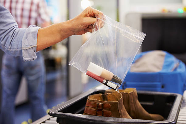 Passenger Puts Liquids Into Bag At Airport Security Check stock photo