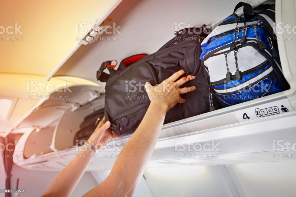 Passenger putting bag to overhead bin space stock photo