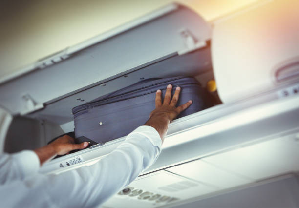 Passenger putting luggage to overhead bin space Passenger putting suitcase to overhead bin space in the airplane carry on luggage stock pictures, royalty-free photos & images