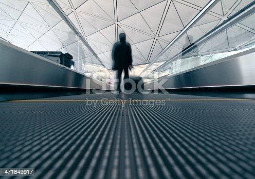istock passenger (Man) rushing through an escalator in airport terminal 471849917