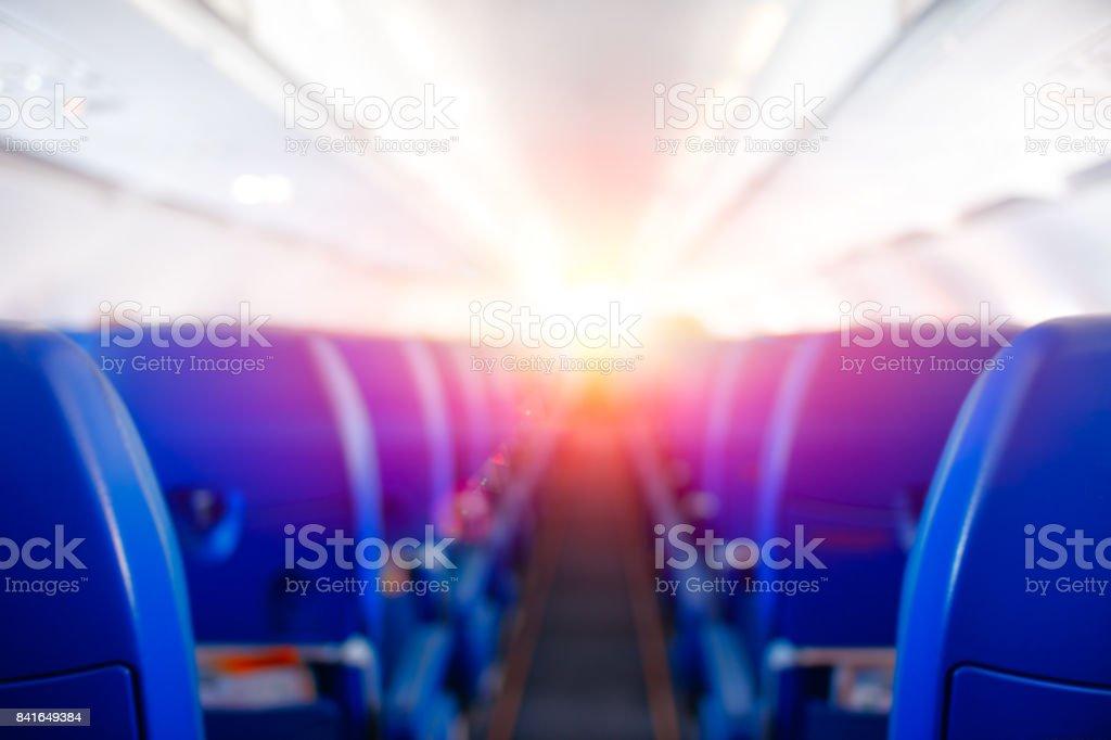 Passenger seat, Interior of airplane, plane flies to meet sun, bright sunlight illuminates the aircraft cabin, travel concept stock photo