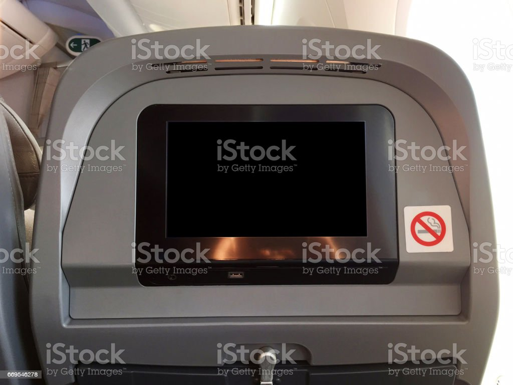 Passenger seat of plane with blank empty black monitor screen, and no smoking allowed sign stock photo