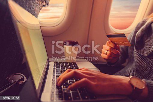 Woman on a flight using credit card for online shopping ++++ Note for the inspector: Credit card is fake and made especially for the photosession ++++