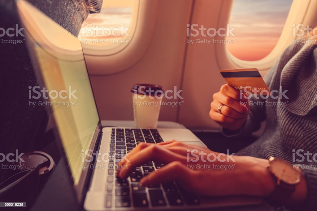 Passenger shopping online with credit card in the airplane stock photo