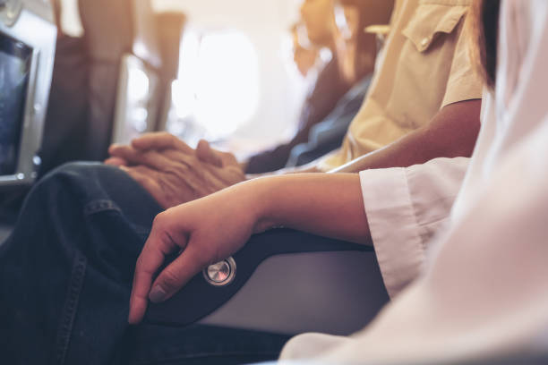 Passenger sitting on a seat row in cabin stock photo