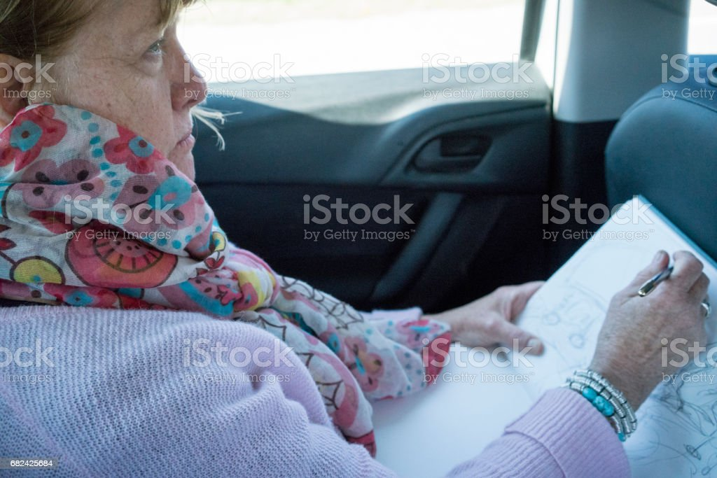Passenger sketching from the backseat of a car royalty-free stock photo