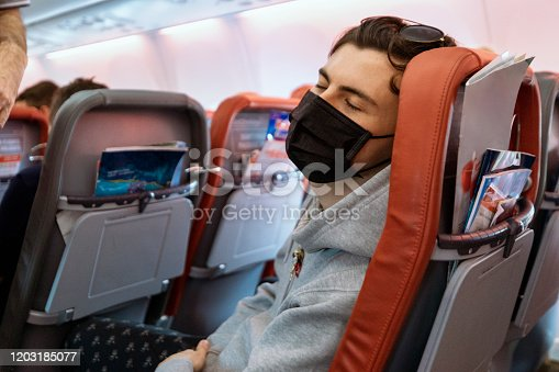 Man sitting on an airplane using his phone while wearing a surgical mask.