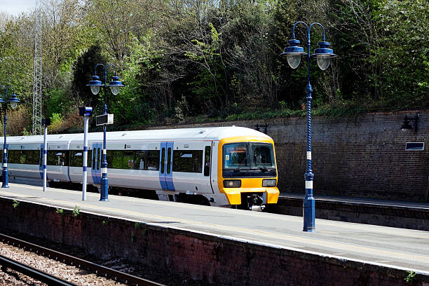 Passenger train entering railway station An electricity-powered passenger train entering a London suburban station on a bright and sunny April day. electric train stock pictures, royalty-free photos & images