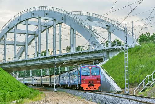 Mytischi, Russia - June 23, 2020: Passenger train moves under the bridge.