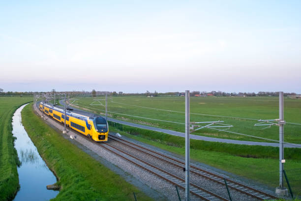Passenger train of the Dutch Railways (NS) driving in a rural landscape stock photo