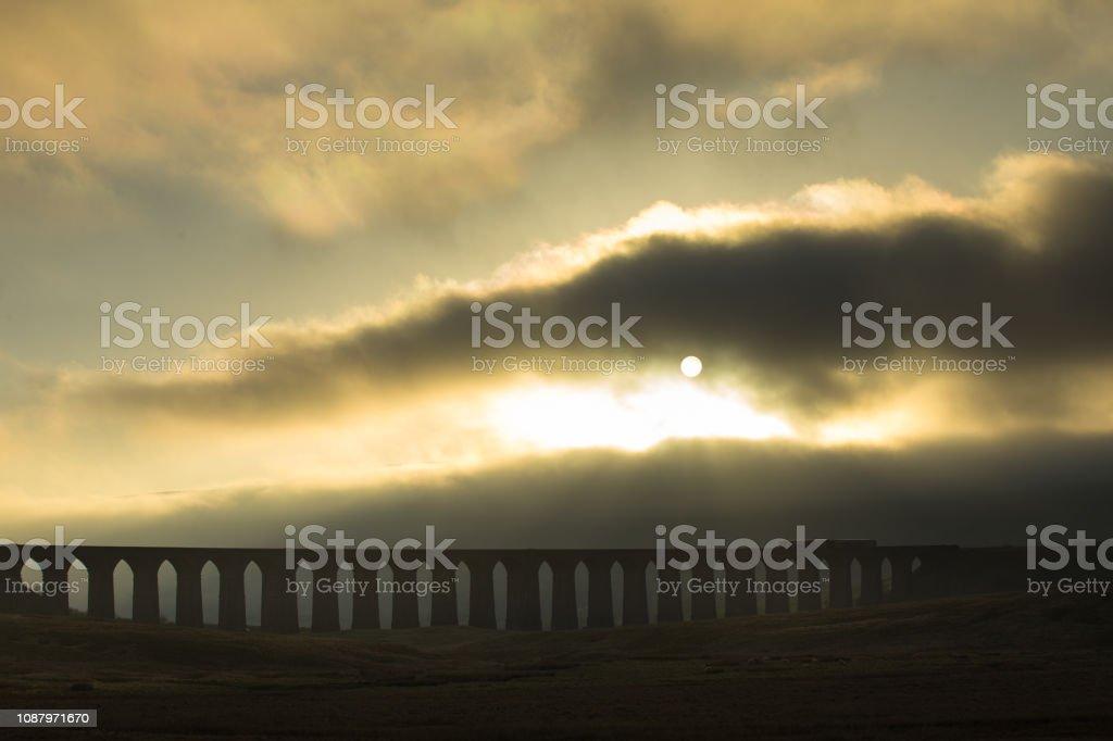 Passenger Train on Ribblehead Viaduct on Foggy Evening stock photo
