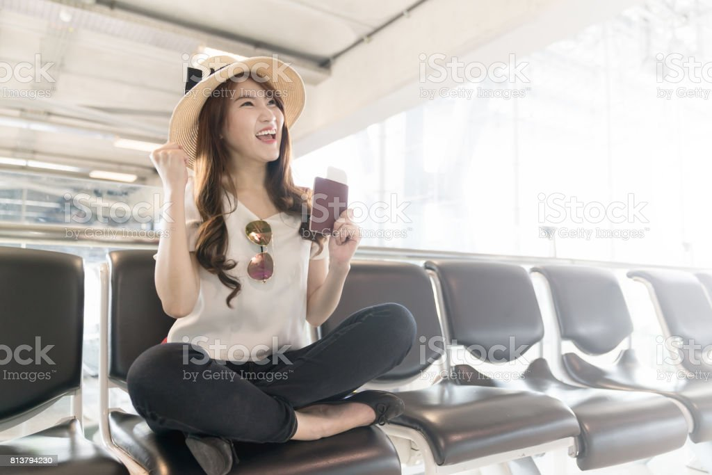 Passenger traveler woman in airport waiting for air travel. Asian woman smiling and holding passport and boarding pass in waiting hall of departure in airport. stock photo