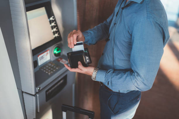 Passenger using credit card at the ATM on airport Businessman with suitcase withdrawing money at the ATM banks and atms stock pictures, royalty-free photos & images