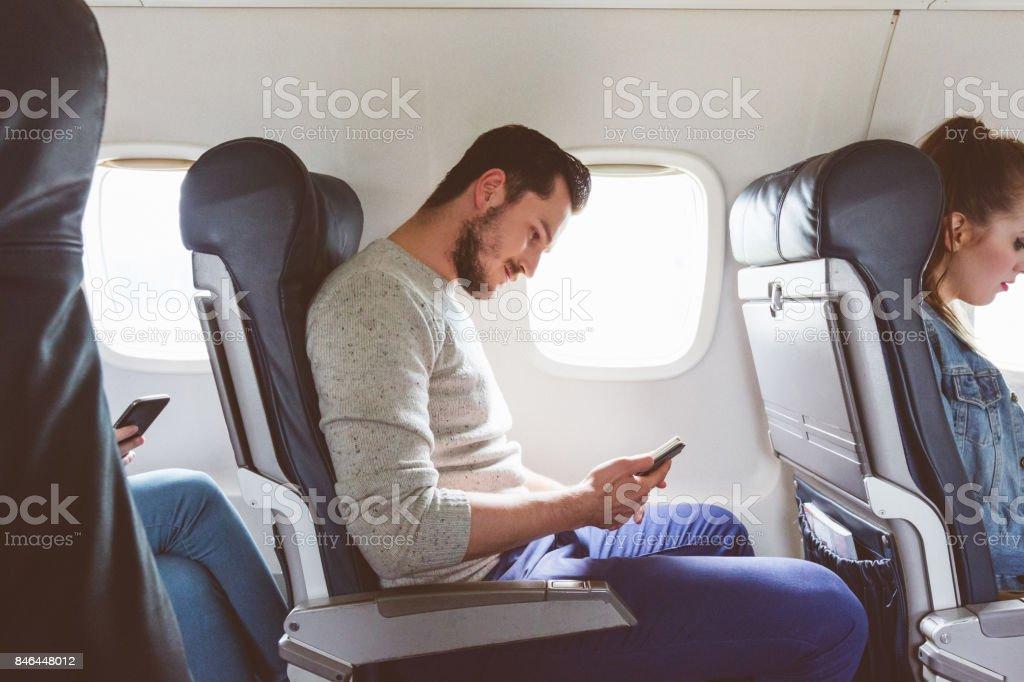 Passagier mit Handy während des Fluges – Foto