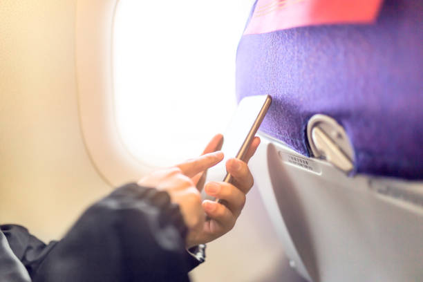 Passenger using mobile phone in aircraft. stock photo