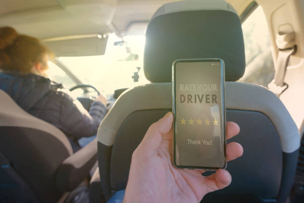 passenger using smart phone app to rate a taxi or modern peer to peer ridesharing driver - rideshare stock photos and pictures