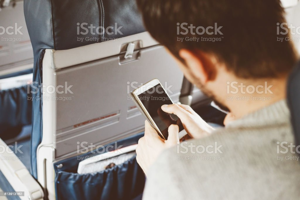 Passenger using smart phone while travelling by airplane stock photo