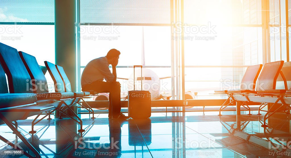 Passenger waits for plane in an airport Man sits down in waiting area in airport terminal. He is ready for take off and looks out of the window at a plane. A suitcase stands before him. Adult Stock Photo