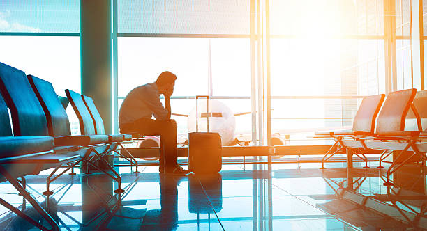 Passenger waits for plane in an airport Man sits down in waiting area in airport terminal. He is ready for take off and looks out of the window at a plane. A suitcase stands before him. jet lag stock pictures, royalty-free photos & images