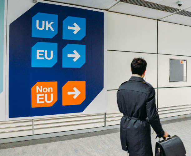 Passenger walks past sign prior to immigration control pass a sign pointing towards queues for UK, EU and Non-EU passport holders. In April 2019, UK is set to leave the European Union - Brexit theme stock photo
