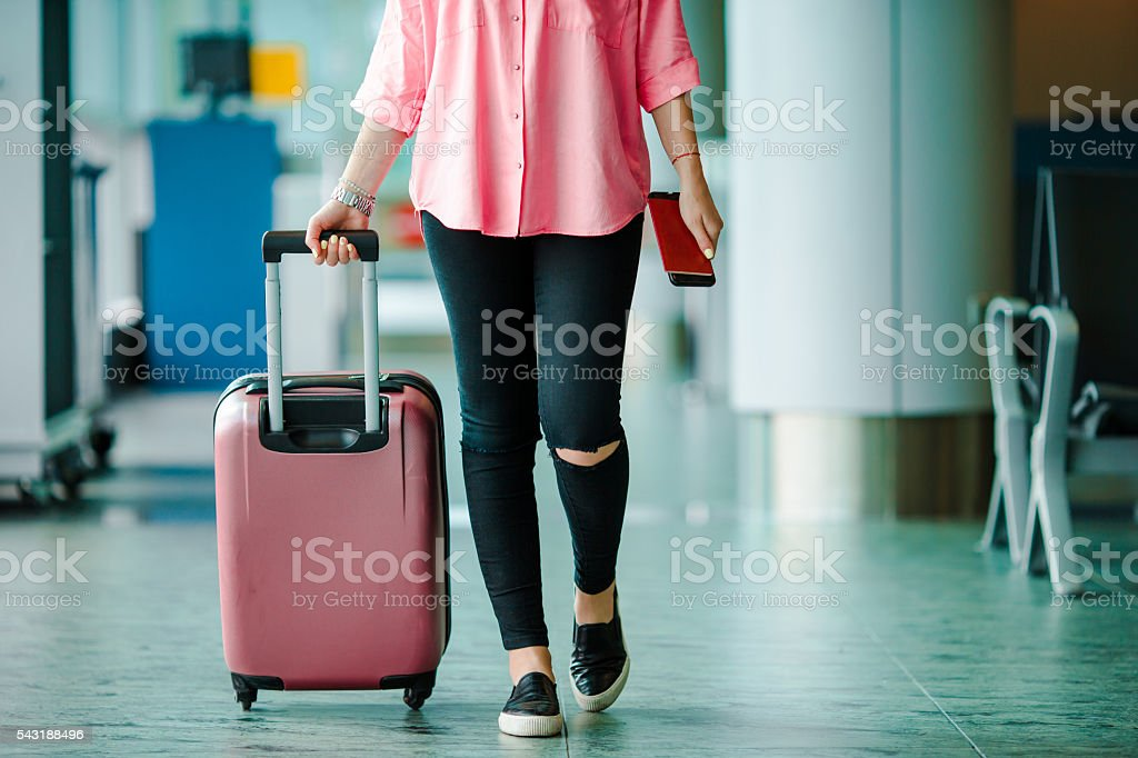 Passenger with passports and boarding pass and pink baggage - Photo